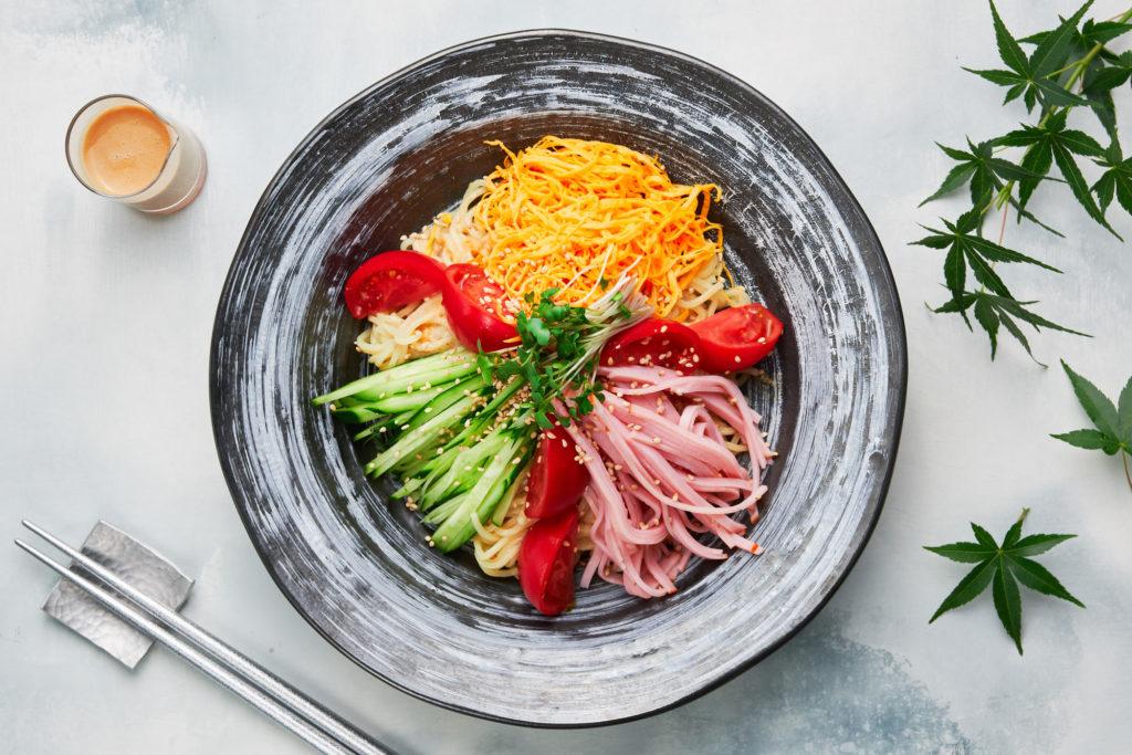 ensalada fria de fideos ramen con tomate, jamón cocido, pepino y tortilla japonesa
