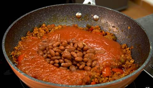 Agregar el tomate y las alubias al chili