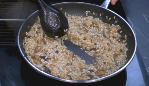 Revolver el risotto de setas hasta que pida caldo